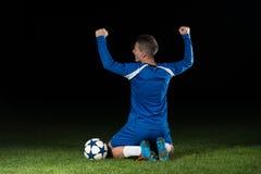 Jugador de fútbol que celebra a Victory On Black Background Fotografía de archivo libre de regalías