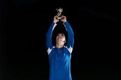 Jugador de fútbol que celebra a Victory While Holding Win Coup Fotos de archivo