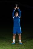 Jugador de fútbol que celebra a Victory While Holding Win Coup Imágenes de archivo libres de regalías
