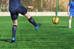 Jugador de fútbol que golpea el balón de fútbol con el pie fotos de archivo