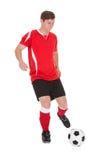 Jugador de fútbol que golpea la bola con el pie Imagenes de archivo