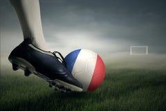 Jugador de fútbol que golpea la bola con el pie hacia posts de la meta Imágenes de archivo libres de regalías