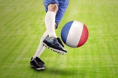 Jugador de fútbol que golpea una bola con el pie en el campo Fotografía de archivo libre de regalías