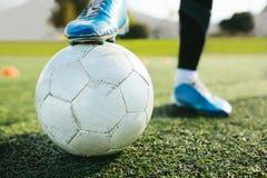 Jugador de fútbol que se coloca en echada con la bola Imagenes de archivo