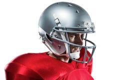 Jugador de fútbol americano confiado en el jersey rojo que mira lejos Fotos de archivo libres de regalías