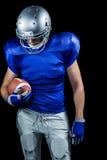 Jugador de fútbol americano que mira abajo mientras que sostiene la bola Imágenes de archivo libres de regalías