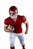 Jugador de fútbol americano que se ejecuta con la bola Imagen de archivo libre de regalías