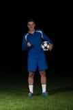 Jugador de fútbol que celebra a Victory On Black Background Imagen de archivo