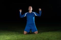 Jugador de fútbol que celebra a Victory On Black Background Fotos de archivo
