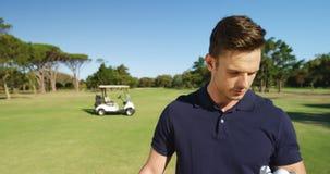 Jugador de golf feliz que examina la pelota de golf almacen de metraje de vídeo