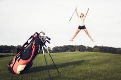 Jugador de golf feliz que salta en campo de golf. Imagen de archivo