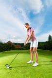 Jugador de golf femenino en el curso que hace el oscilación del golf Fotografía de archivo libre de regalías