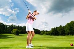Jugador de golf femenino en el curso que hace el oscilación del golf Foto de archivo libre de regalías