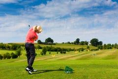 Jugador de golf femenino joven en el campo de prácticas Foto de archivo libre de regalías