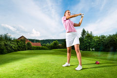 Jugador de golf femenino joven en el curso que hace el oscilación del golf Fotografía de archivo
