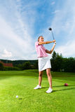 Jugador de golf femenino joven en el curso que hace el oscilación del golf imagen de archivo
