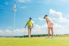 Jugador de golf femenino listo para golpear la bola Imagenes de archivo