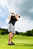 Jugador de golf joven en el curso que hace el oscilación del golf Fotos de archivo libres de regalías
