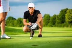 Jugador de golf joven en el curso que pone y que apunta Fotos de archivo libres de regalías