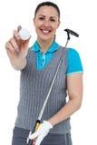 Jugador de golf que celebra un club de golf y una pelota de golf Fotografía de archivo