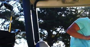 Jugador de golf que consigue en el cochecillo del golf almacen de video