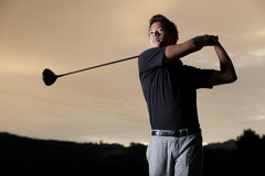 Jugador de golf que junta con te apagado en la puesta del sol. Foto de archivo