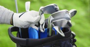 Jugador de golf que pone al club de golf en bolso metrajes