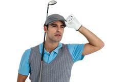 Jugador de golf que presenta con el club de golf Fotografía de archivo
