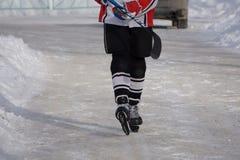 Jugador de hockey con el palillo en el hielo fotografía de archivo