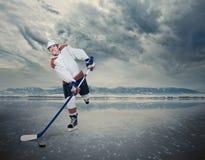 Jugador de hockey en la superficie del lago del hielo Foto de archivo libre de regalías