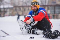 Jugador de hockey que se sienta en el hielo para atar cordones Imagenes de archivo