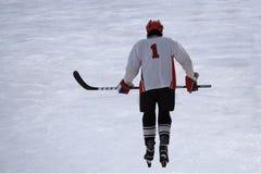 Jugador de hockey solo que va a reducir drásticamente el duende malicioso en la pista de patinaje al aire libre imagenes de archivo