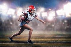 Jugador de la mujer del fútbol americano en la acción atleta en el equipo imagenes de archivo
