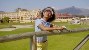 Jugador de la mujer joven en un campo de golf de la orilla del mar almacen de video