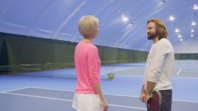 Jugador de los saludos del instructor en el campo de tenis almacen de video
