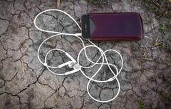 Jugador de música móvil en la tierra agrietada Imagenes de archivo
