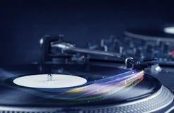 Jugador de música que juega música del vinilo con las líneas abstractas coloridas Imagenes de archivo