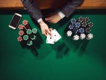 Jugador de póker con smartphone Foto de archivo libre de regalías