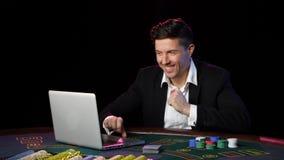 Jugador de póker en línea feliz que gana en casino Cierre para arriba almacen de video