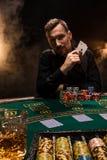 Jugador de póker hermoso con dos as en sus manos y microprocesadores que se sientan en la tabla del póker en un cuarto oscuro por Imagen de archivo