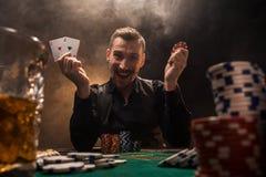 Jugador de póker hermoso con dos as en sus manos y microprocesadores que se sientan en la tabla del póker en un cuarto oscuro por Imágenes de archivo libres de regalías