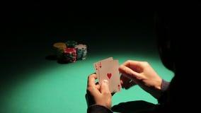 Jugador de póker que coge buenas tarjetas del distribuidor autorizado, juego afortunado para el adicto de juego almacen de video