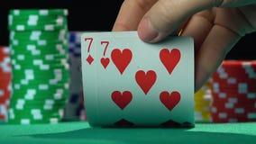 Jugador de póker que muestra un par de sevens, número afortunado, mano que gana Cámara lenta metrajes