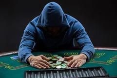 Jugador de póker que toma las fichas de póker después de ganar Fotografía de archivo