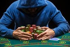 Jugador de póker que toma las fichas de póker después de ganar Imagen de archivo libre de regalías