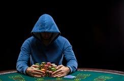 Jugador de póker que toma las fichas de póker después de ganar Imagenes de archivo