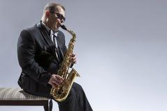 Jugador de saxofón caucásico relajado y pensativo maduro en las gafas de sol que tocan el saxofón fotos de archivo libres de regalías