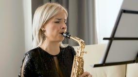Jugador de saxofón del jazz que se realiza en el saxofón en la sala de estar almacen de metraje de vídeo