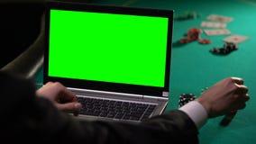 Jugador de sexo masculino que apuesta el póker en línea al ordenador portátil, sosteniendo dados afortunados, pantalla verde almacen de video