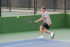 Jugador de tenis aprisa en conseguir a la bola Imagen de archivo